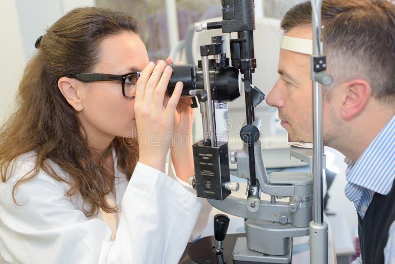 女性验光师审查的患者眼睛 免版税库存照片