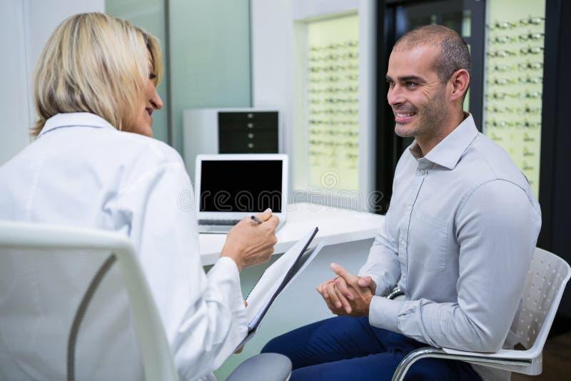 女性验光师谈话与男性患者 免版税库存照片