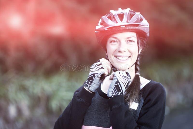 女性骑自行车的人佩带的自行车盔甲 免版税图库摄影