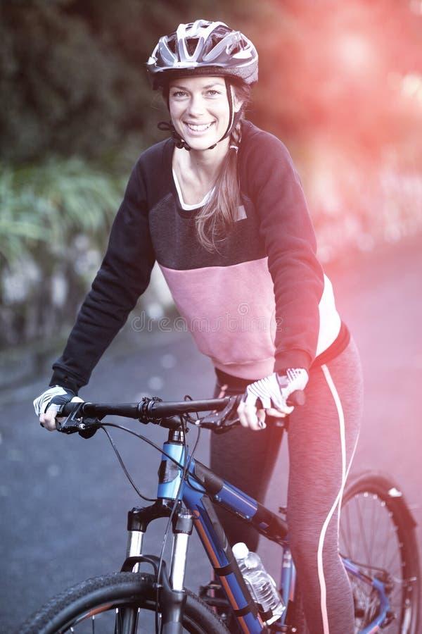 女性骑自行车的人画象有登山车的在乡下 免版税库存照片