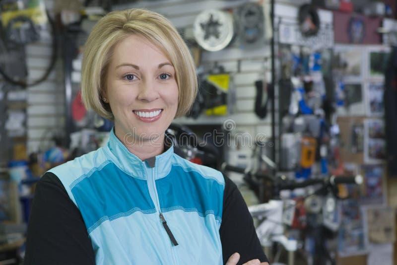 女性骑自行车者在商店 免版税库存图片