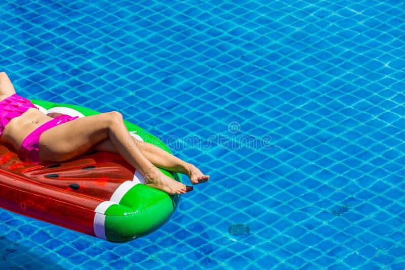 女性鸟瞰图说谎在一个浮动床垫的比基尼泳装的  免版税库存照片
