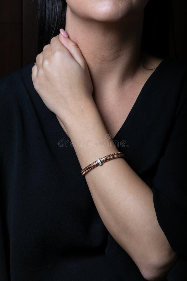 女性,柳条,从玫瑰色金子的镯子与金刚石在中部在妇女手上,在黑背景 免版税库存照片