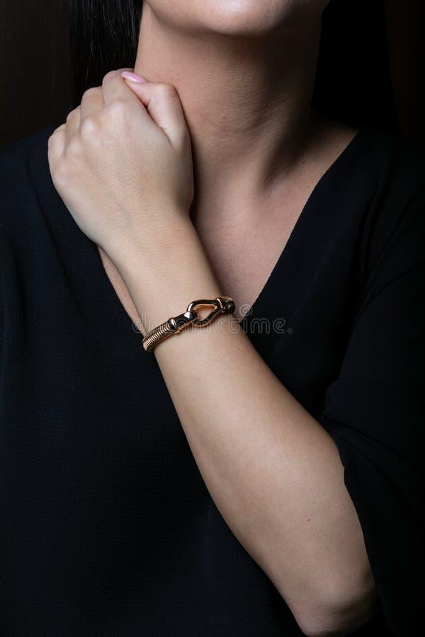 女性,柳条,从玫瑰色金子的镯子与carabiner在中部在妇女手上,在黑背景 库存图片