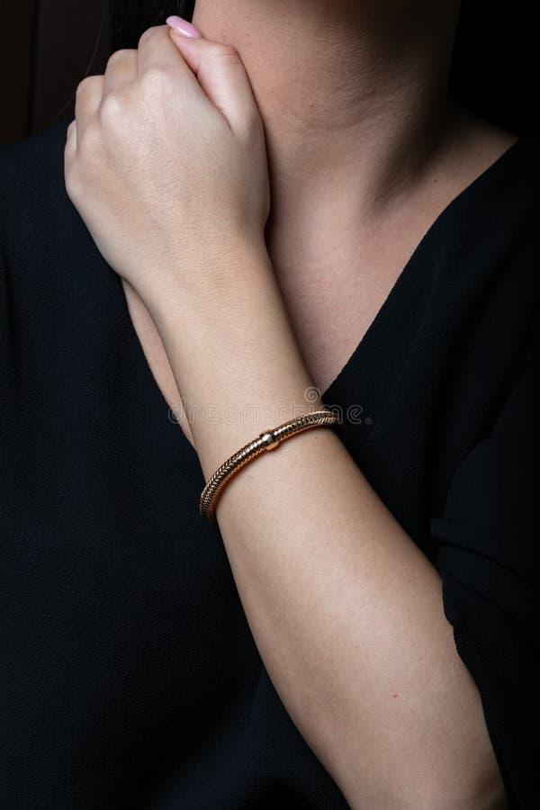 女性,玫瑰色有插入物的金柳条镯子在中部,在手边,在黑背景 免版税库存图片