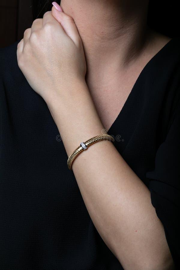 女性,玫瑰色有银色插入物的金柳条镯子与金刚石,在中部,在手边,在黑背景 库存照片