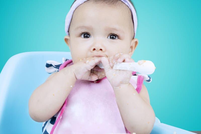 女性婴儿咬住粥匙子 库存照片