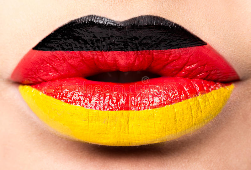 女性嘴唇关闭与德国的图片旗子 黑,红色,黄色 免版税图库摄影