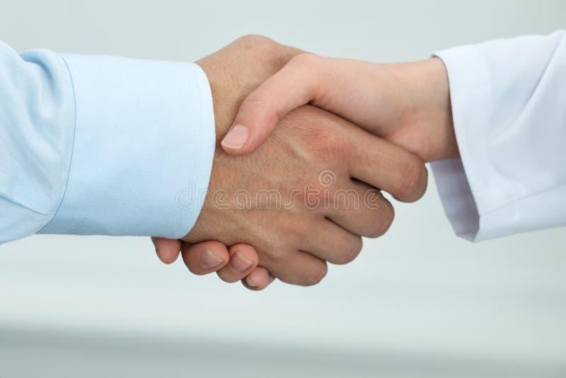 女性医学医生与男性患者握手 免版税库存图片
