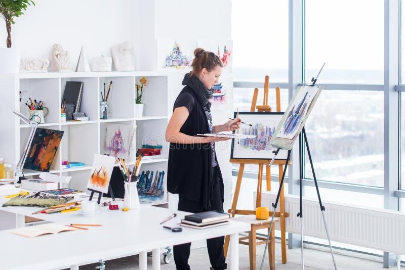 女性画家图画在使用画架的艺术演播室 一张少妇绘画的画象与水彩画油漆的在白色 免版税库存照片