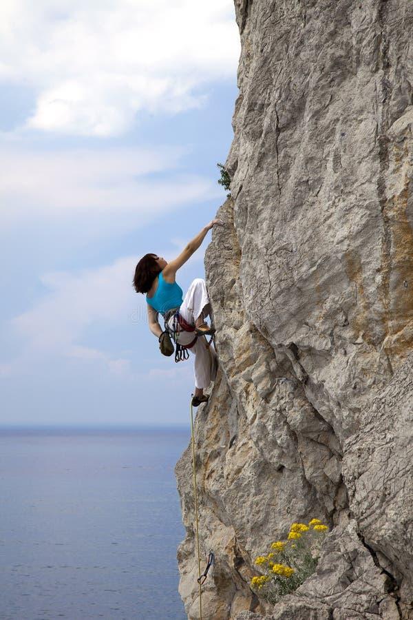 女性登山人攀登墙壁完全成功在海 免版税库存图片