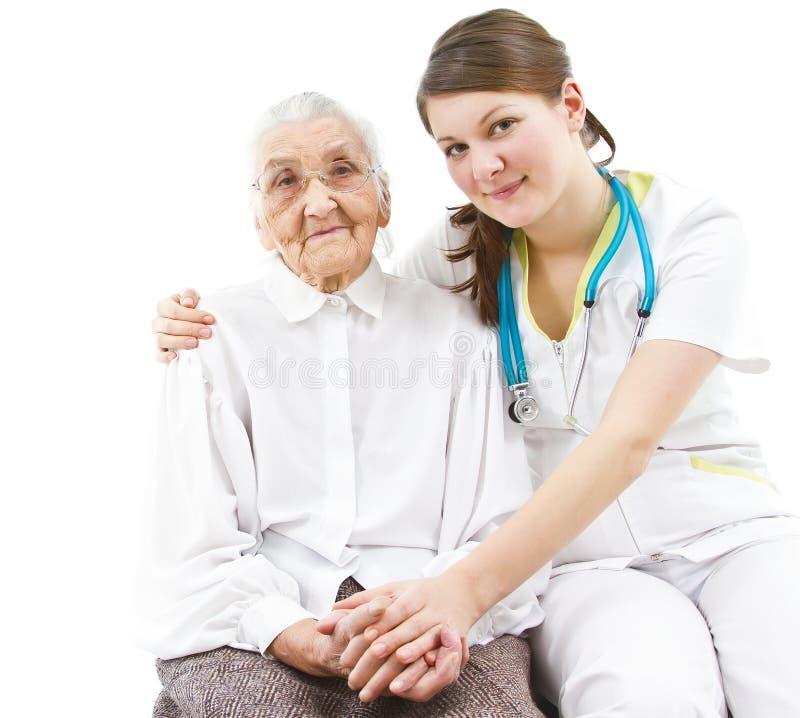 照顾一个老妇人的医生 免版税库存图片