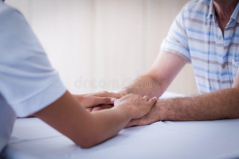 女性医生可安慰的老人的中间部分在客厅 图库摄影