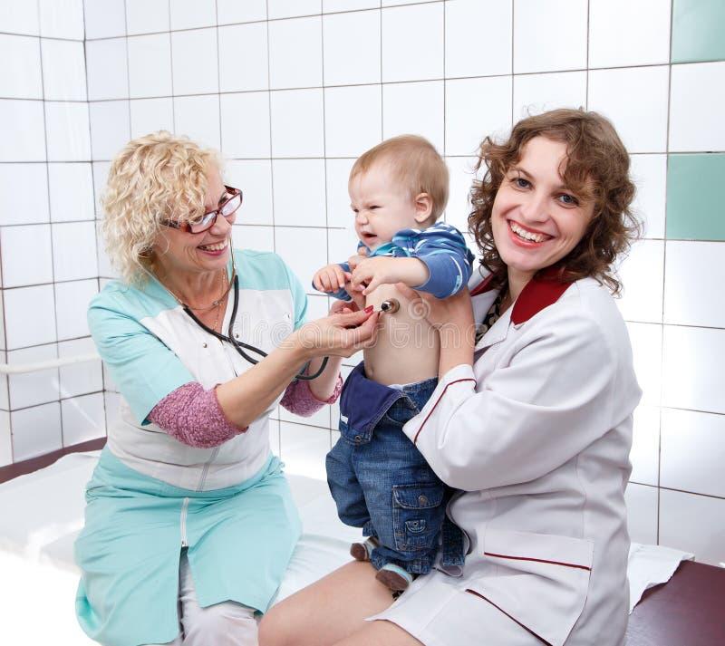 女性医生和护士审查小恼怒的婴孩 免版税库存照片