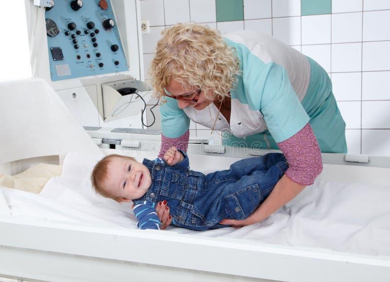 女性医生在长沙发上把小男孩放 库存图片