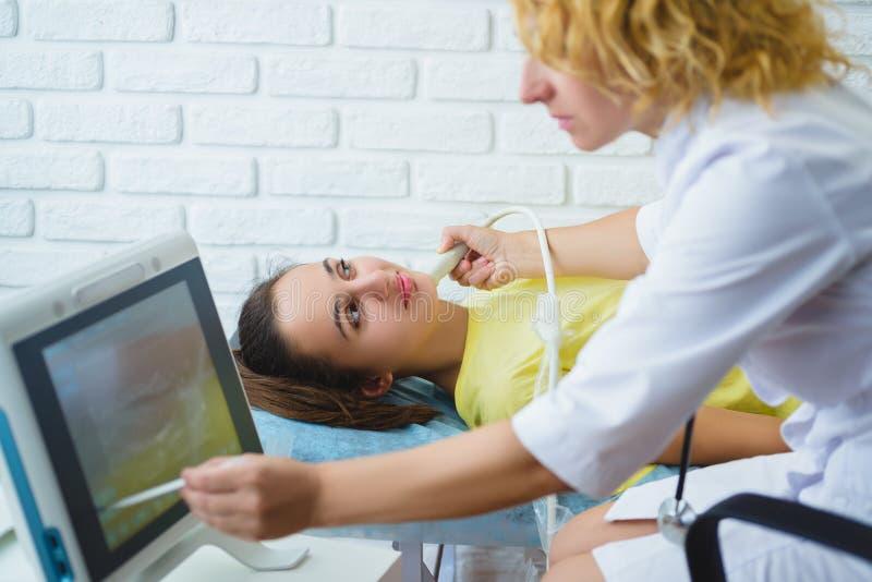 女性医生审查女孩与超声波的淋巴结在医疗中心 图库摄影