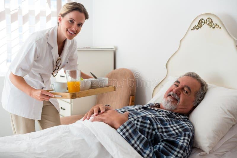 女性医生服务食物画象对资深耐心放松的在床上 免版税库存照片