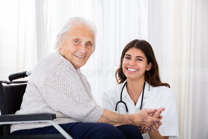 女性医生With Disabled Senior Patient在医院 免版税库存照片
