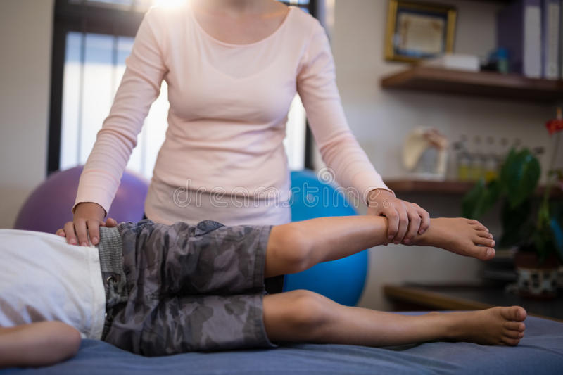 女性治疗师审查的男孩的低部分 图库摄影