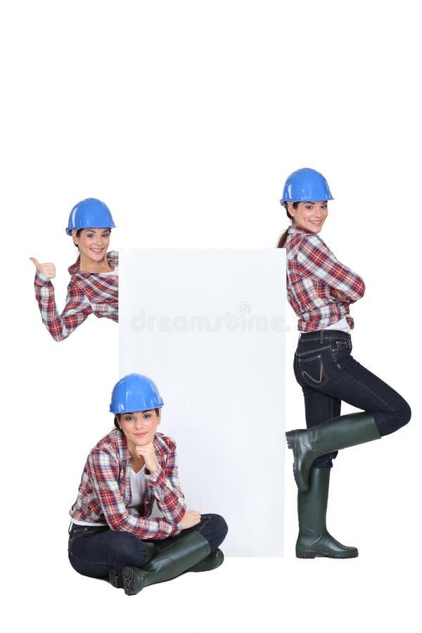 女性建造者站立与广告 免版税图库摄影
