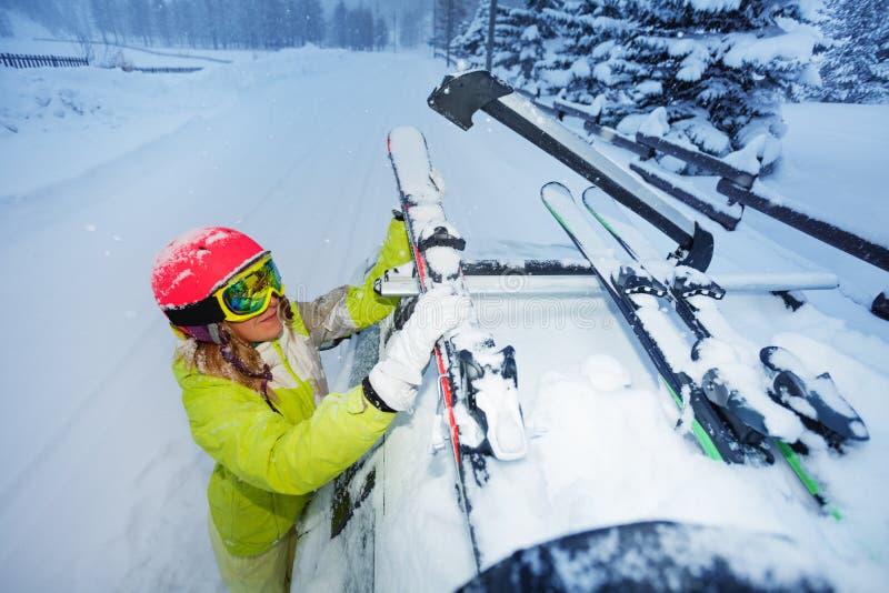 女性滑雪者紧固滑雪到汽车屋顶` s路轨 库存图片