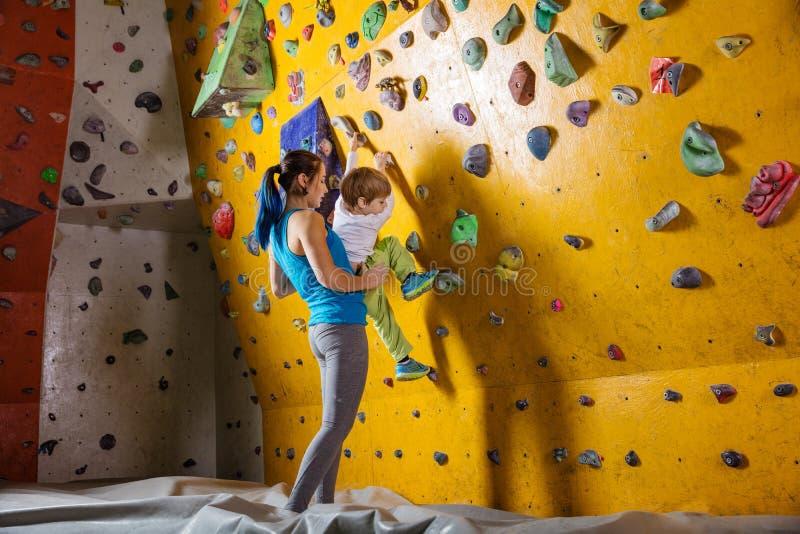 年轻女性bouldering的辅导员帮助的男孩上升 库存图片
