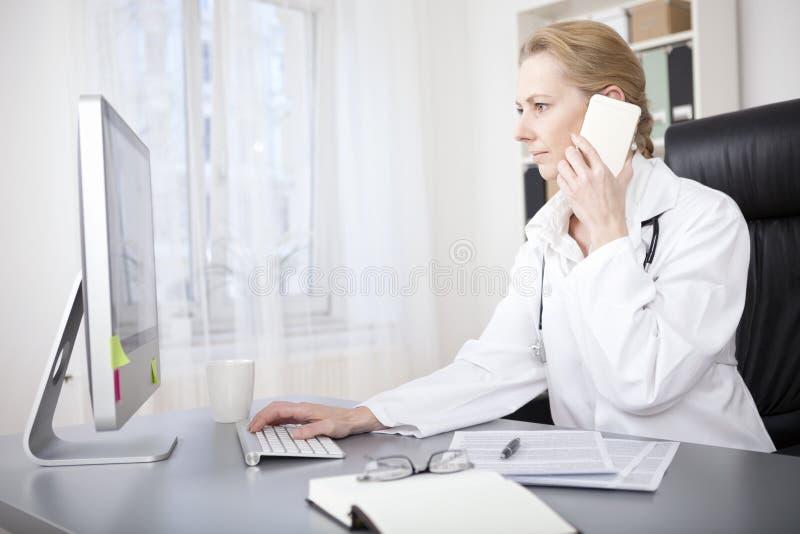 女性Calling Phone While Using医生计算机 免版税库存图片