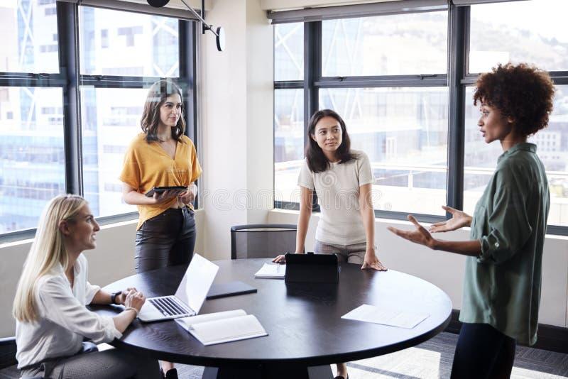女性creatives在听他们的同事的候选会议地点做一个不拘形式的介绍 免版税图库摄影
