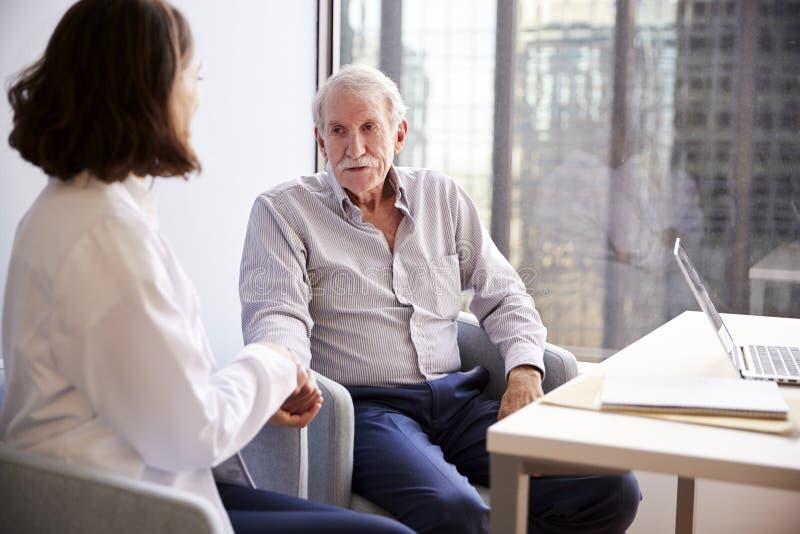 女性In Office Reassuring医生老人患者和握他的手 库存图片