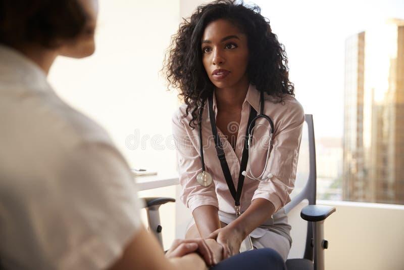女性In Office Reassuring Woman医生患者和握她的手 免版税库存照片