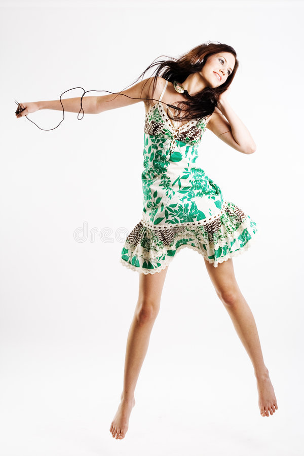 女性jamping的音乐 免版税库存图片