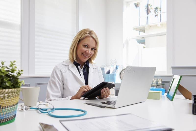 女性Sitting At Desk Using数字式医生片剂在办公室 图库摄影