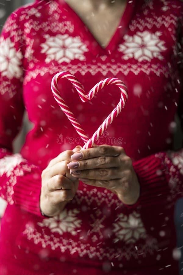 女手拿着两根心形圣诞糖果 免版税库存图片