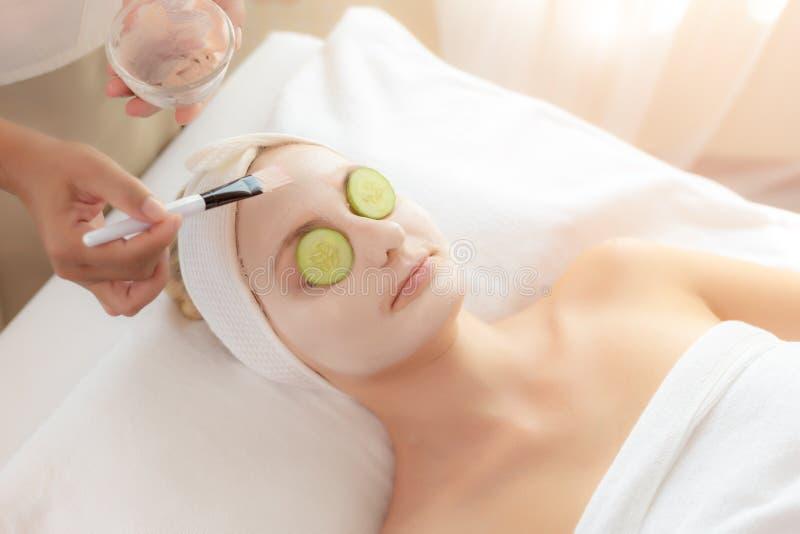 女按摩师或按摩治疗师应用的奶油色面具用途刷子于健康皮肤面孔的美丽的顾客面孔用黄瓜 免版税图库摄影