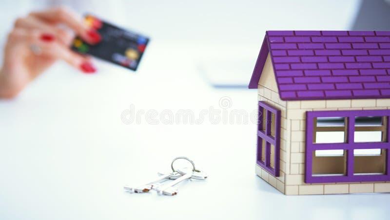 女推销员举行一张信用卡和计算卖新的房屋贷款的价格 式样私有房子和钥匙在 免版税图库摄影