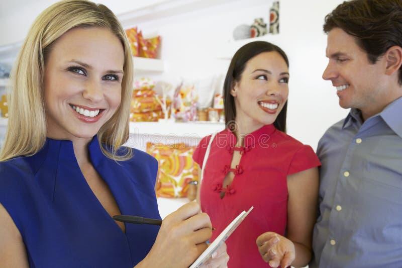 女推销员和夫妇在商店 库存图片