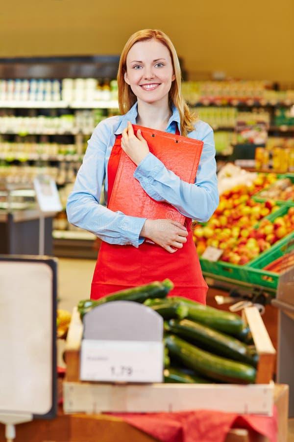 年轻女推销员在有机食品商店 库存图片