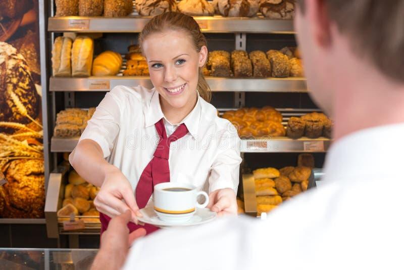 女推销员在给咖啡的面包师的商店顾客 库存照片