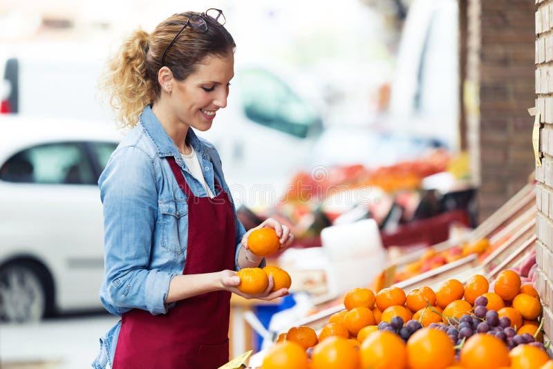 女推销员选择新鲜水果和为在健康杂货店的工作日做准备 免版税图库摄影