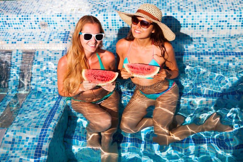 女朋友举行一半在一个蓝色水池的一个红色西瓜,放松 免版税库存照片