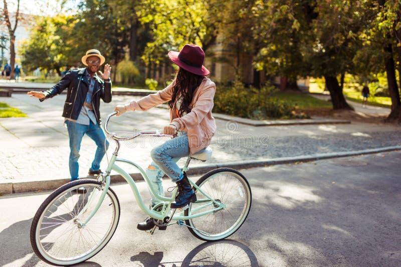 女朋友做鬼脸骑马的自行车和的男朋友 库存图片
