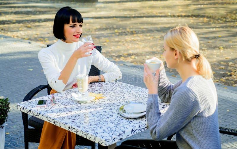 女朋友喝咖啡和谈话 真实的友谊友好的密切关系 两名妇女咖啡馆大阳台的交谈 免版税库存照片