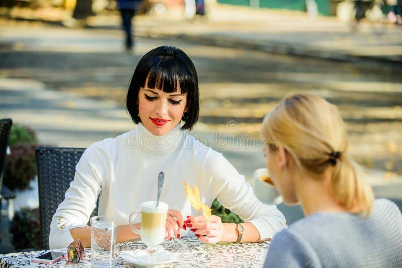 女朋友喝咖啡谈话 交谈妇女咖啡馆大阳台 友谊友好的联系 揭示和支持 图库摄影