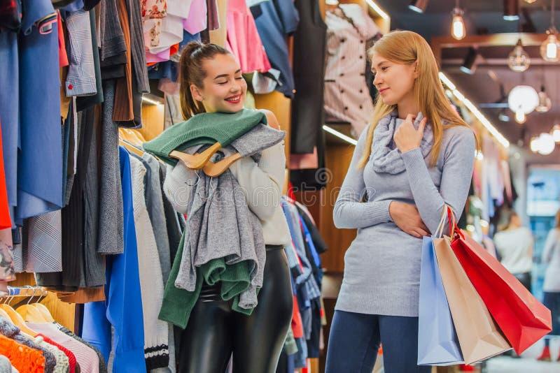 女朋友在商店 一拿着购物带来 免版税库存图片