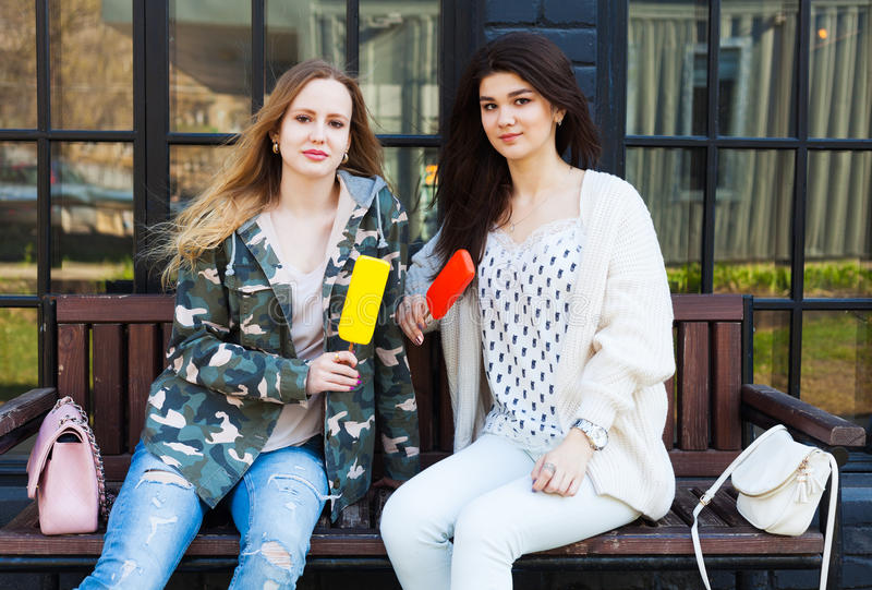 女朋友在时尚成套装备打扮的两个女孩休息,吃冰淇凌 爱斯基摩-阿留申语 免版税库存图片