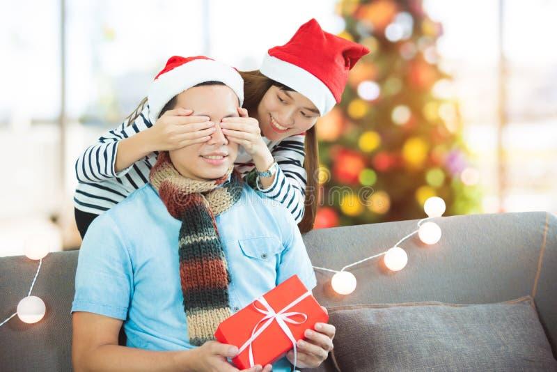 女朋友惊奇男朋友通过在家给在沙发的圣诞礼物有xmas装饰树的 库存照片