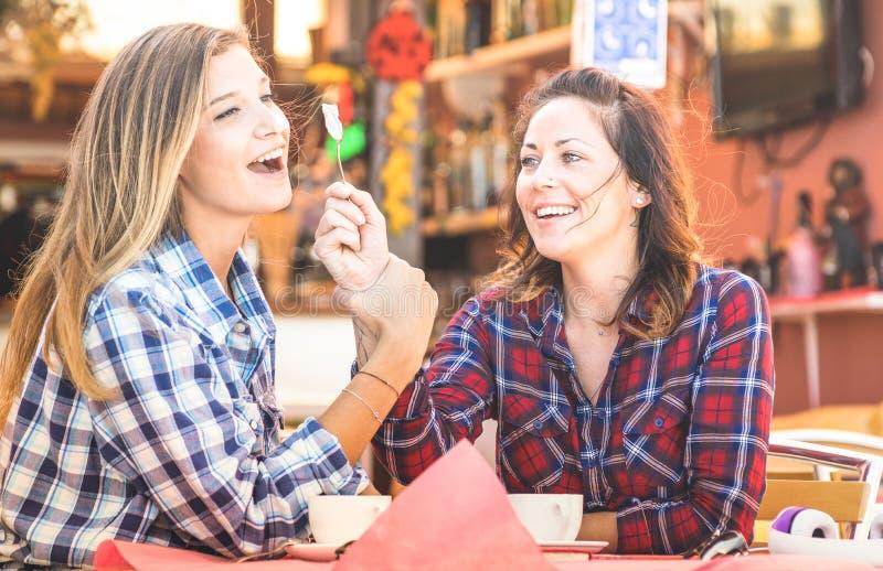 女朋友愉快的夫妇饮用的热奶咖啡和一起笑-与获得的年轻女人的住处概念谈和乐趣 库存照片