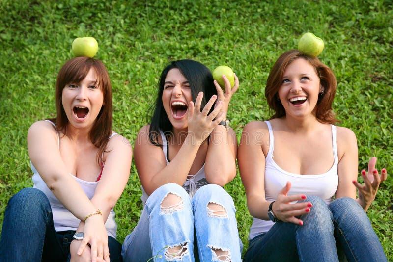 女朋友用苹果在公园 免版税库存图片