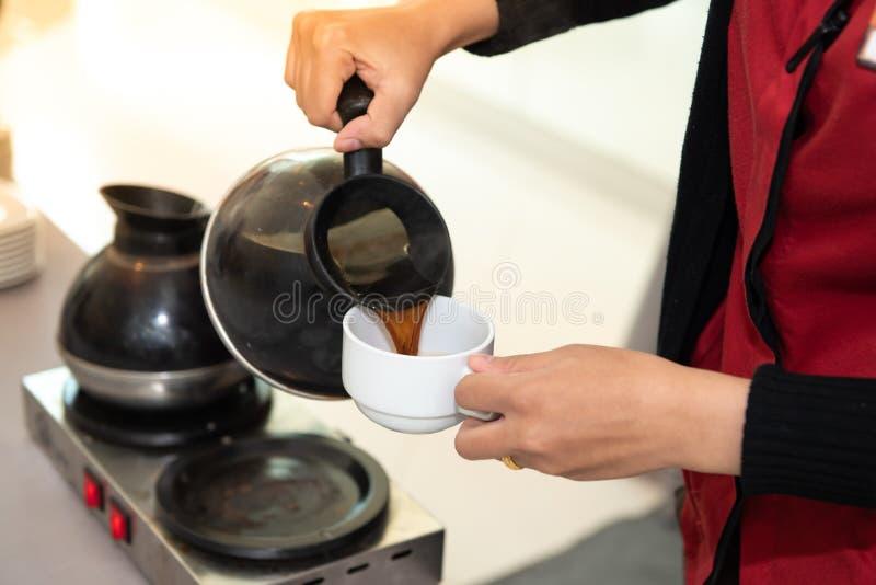 女服务员倒咖啡 免版税图库摄影