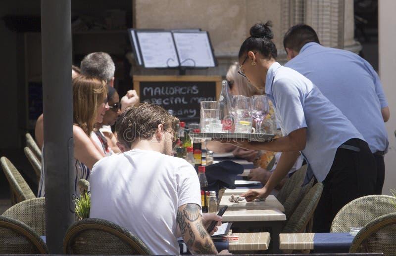 女服务员在旅游大阳台酒吧细节的服务饮料 免版税图库摄影